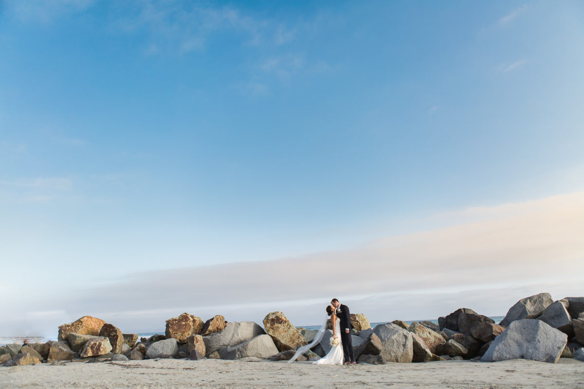 bride and groom kissing on beach in san diego