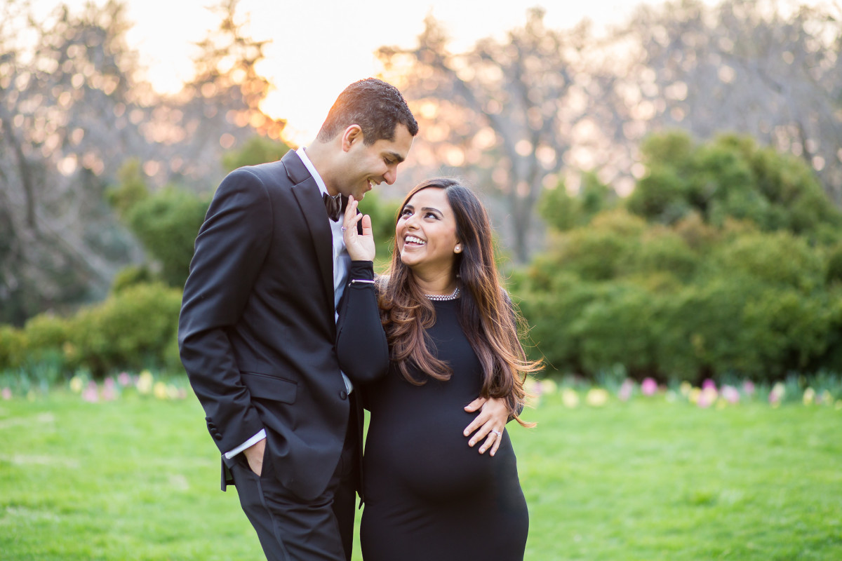 pregnant mom in black dress and husband in tuxedo